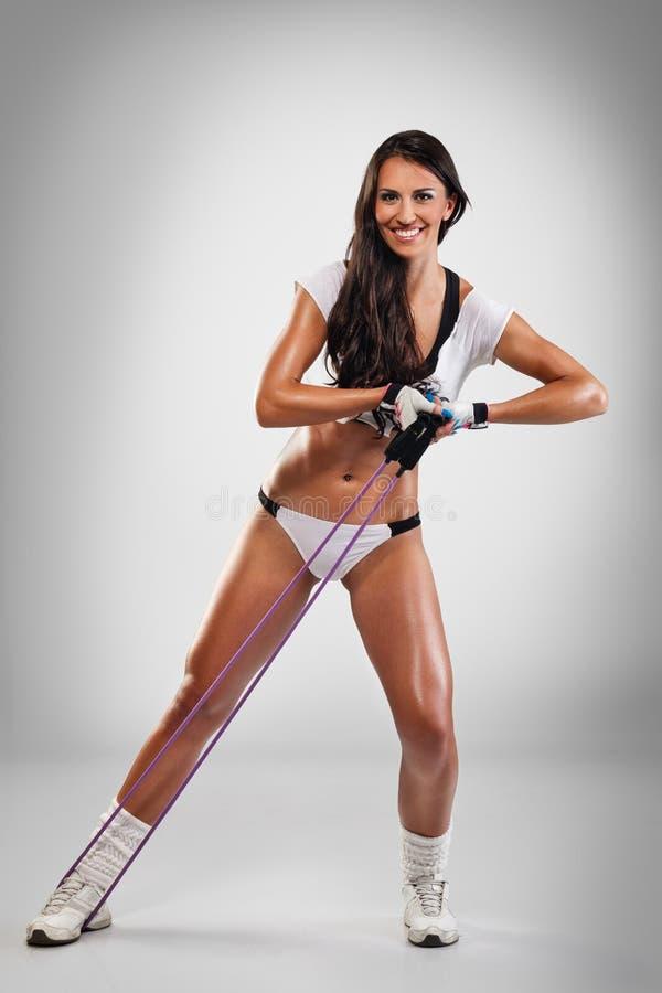 Προκλητική άσκηση γυναικών με την ελαστική ζώνη στοκ εικόνες