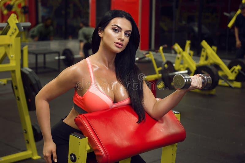 Προκλητική γυναίκα ικανότητας που κάνει τον αθλητισμό workout στη γυμναστική με τους αλτήρες στοκ φωτογραφίες