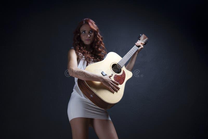 Προκλητική γυναίκα κιθαριστών στοκ εικόνα
