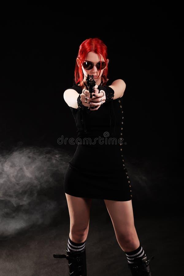 Προκλητική γυναίκα με ένα πυροβόλο όπλο στοκ εικόνες