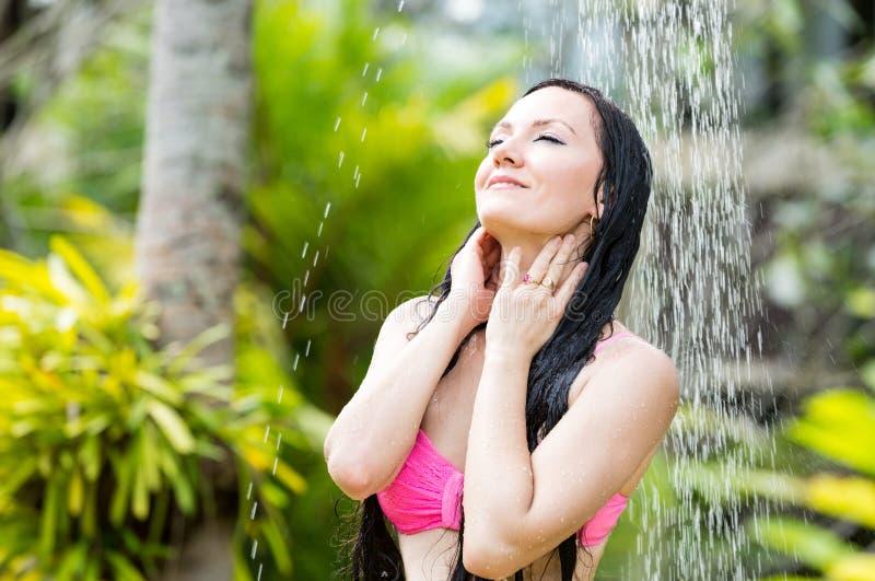 Προκλητική γυναίκα με μακρυμάλλη στο μπικίνι κάτω από το ντους στην τροπική παραλία στοκ εικόνες