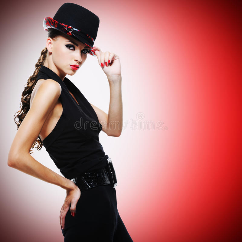 Προκλητική γυναίκα με τα κόκκινα χείλια και τα καρφιά στο σύγχρονο μαύρο καπέλο στοκ φωτογραφίες με δικαίωμα ελεύθερης χρήσης