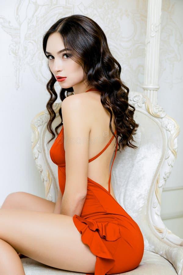 Προκλητική γυναίκα με το μακρυμάλλες φορώντας κόκκινο φόρεμα με τις μπούκλες Hairstyle κυμάτων στοκ φωτογραφία με δικαίωμα ελεύθερης χρήσης