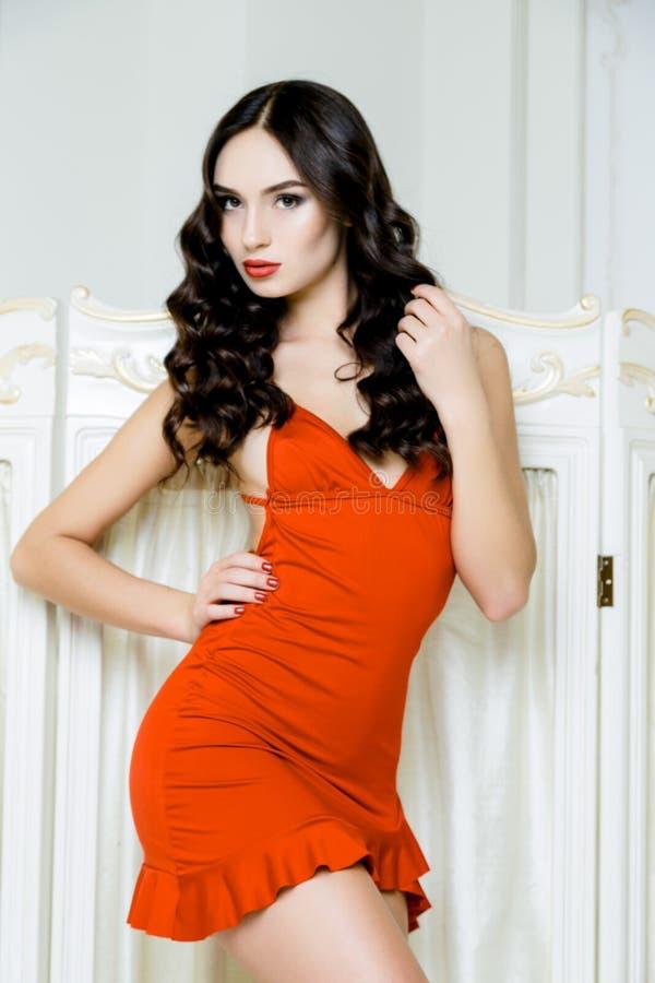 Προκλητική γυναίκα με το μακρυμάλλες φορώντας κόκκινο φόρεμα με τις μπούκλες Hairstyle κυμάτων στοκ εικόνες
