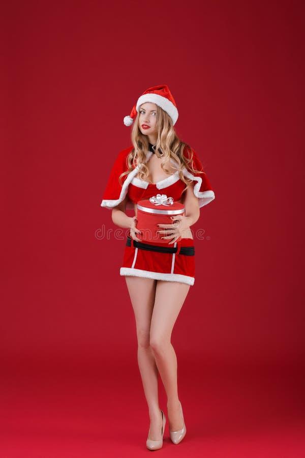 Προκλητική γυναίκα που φορά τα ενδύματα Άγιου Βασίλη με το δώρο Χριστουγέννων στοκ εικόνα