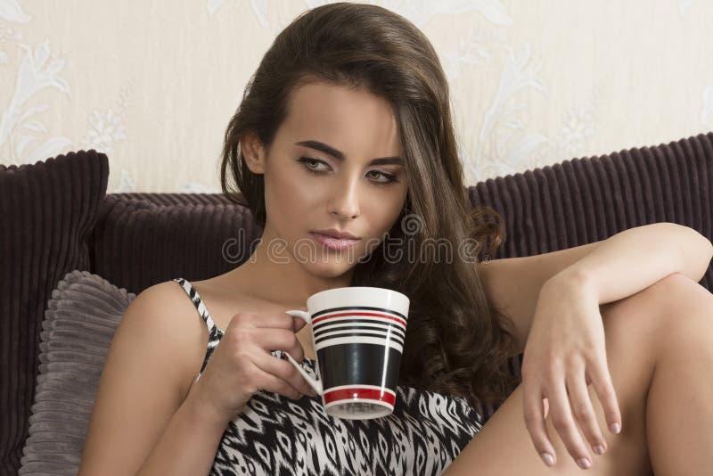 Προκλητική γυναίκα στον καναπέ με το φλυτζάνι στοκ εικόνα