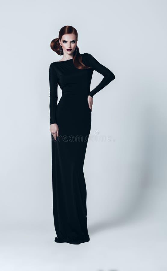 Προκλητική γυναίκα στο πολύ μαύρο φόρεμα στοκ φωτογραφίες