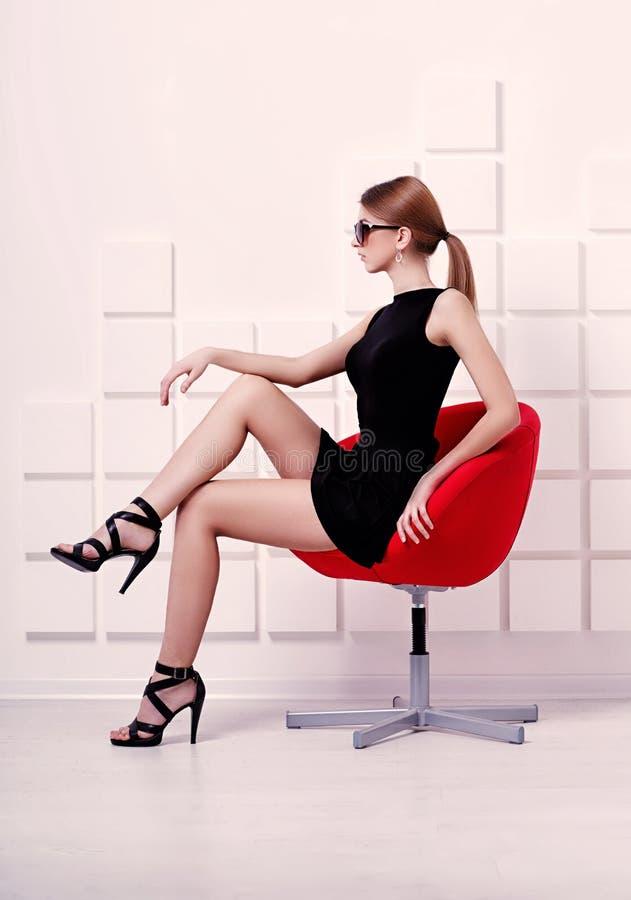προκλητική γυναίκα συνεδρίασης εδρών πλάνο μόδας στοκ εικόνα
