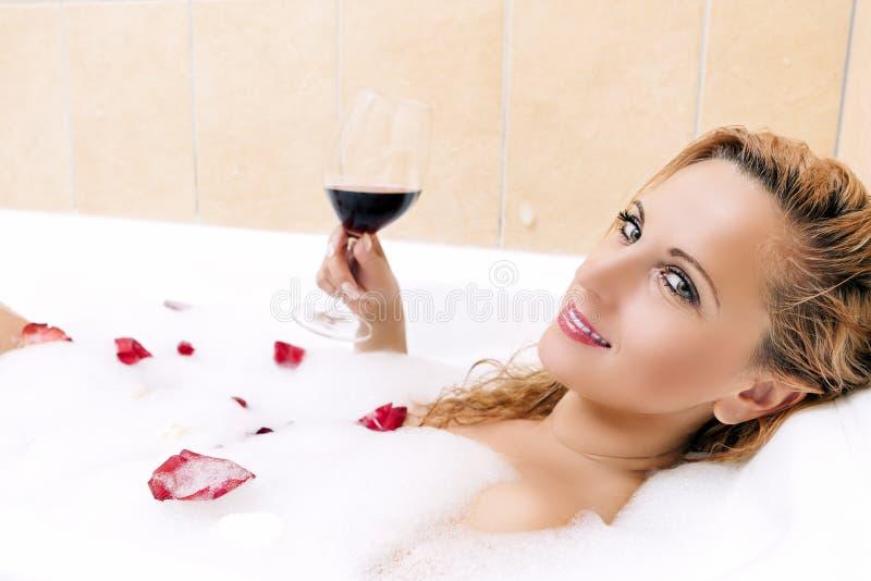 Προκλητική και αισθησιακή ξανθή θηλυκή χαλάρωση στο Foamy λουτρό στοκ εικόνες