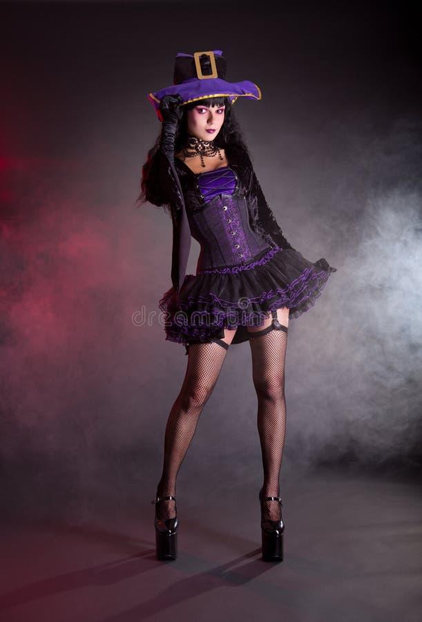 Προκλητική μάγισσα στο πορφυρό και μαύρο γοτθικό κοστούμι αποκριών στοκ εικόνα με δικαίωμα ελεύθερης χρήσης