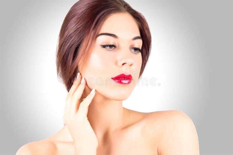 Προκλητική νέα γυναίκα με τα όμορφα κόκκινα χείλια που κοιτάζει κάτω στο γκρίζο υπόβαθρο Γυναίκα ομορφιάς με τα κόκκινα χείλια σχ στοκ φωτογραφία