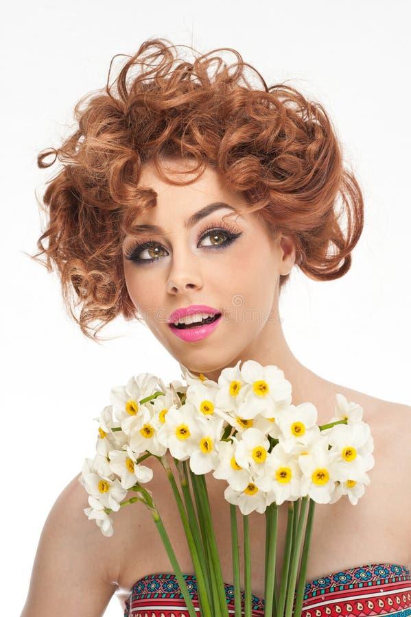 Προκλητική νέα γυναίκα με τα όμορφα μπλε μάτια με τα φωτεινά άσπρα λουλούδια στοκ εικόνες