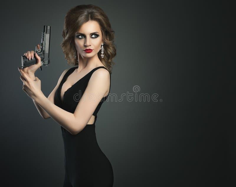 Προκλητική νέα γυναίκα ομορφιάς με το πυροβόλο όπλο σε ένα σκοτεινό πορτρέτο του BG στοκ εικόνες