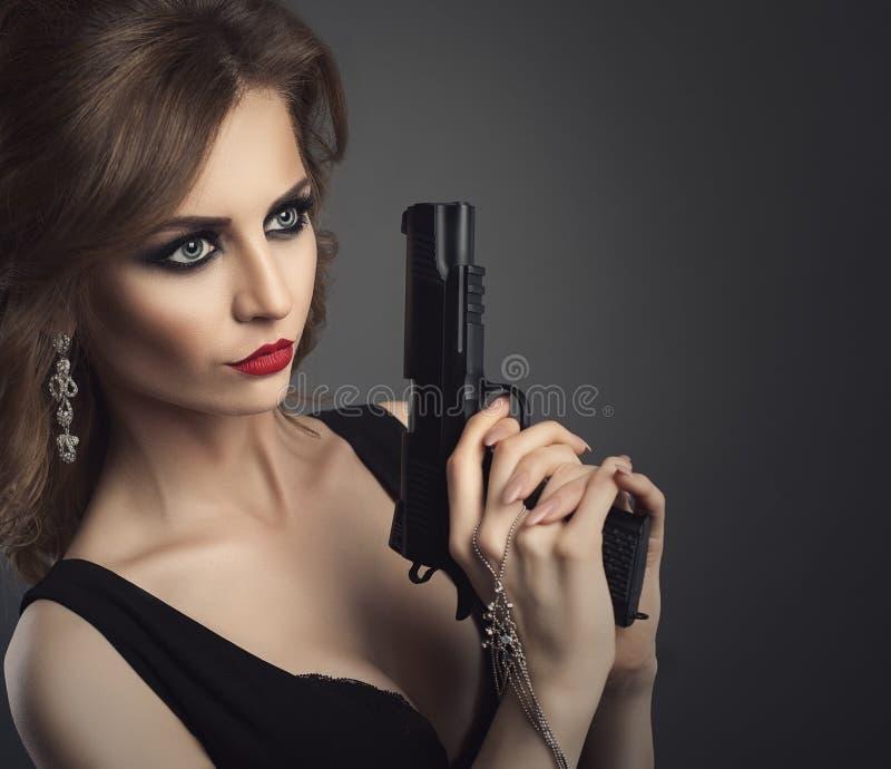 Προκλητική νέα γυναίκα ομορφιάς με το στενό επάνω πορτρέτο πυροβόλων όπλων στοκ εικόνες