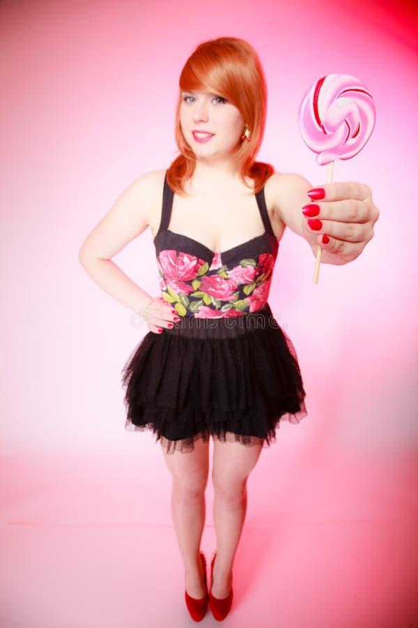 Προκλητική νέα γυναίκα που παρουσιάζει καραμέλα. Κορίτσι Redhair που δίνει το γλυκό lollipop στοκ φωτογραφία με δικαίωμα ελεύθερης χρήσης