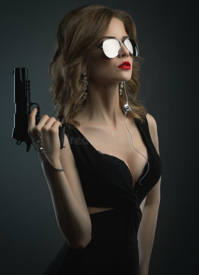 Προκλητική νέα γυναίκα στον πυροβολισμό στούντιο πυροβόλων όπλων εκμετάλλευσης γυαλιού ήλιων καθρεφτών στοκ φωτογραφίες