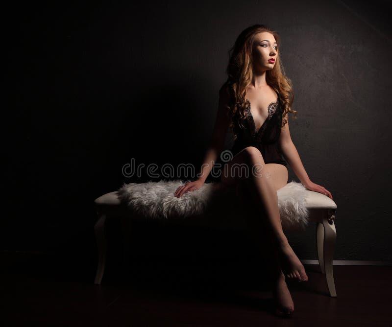 Προκλητική νέα όμορφη γυναίκα αισθησιακό μαύρο lingerie, που κάθεται στον άσπρο πάγκο με τη γούνα, χωρίς παπούτσια στοκ εικόνες