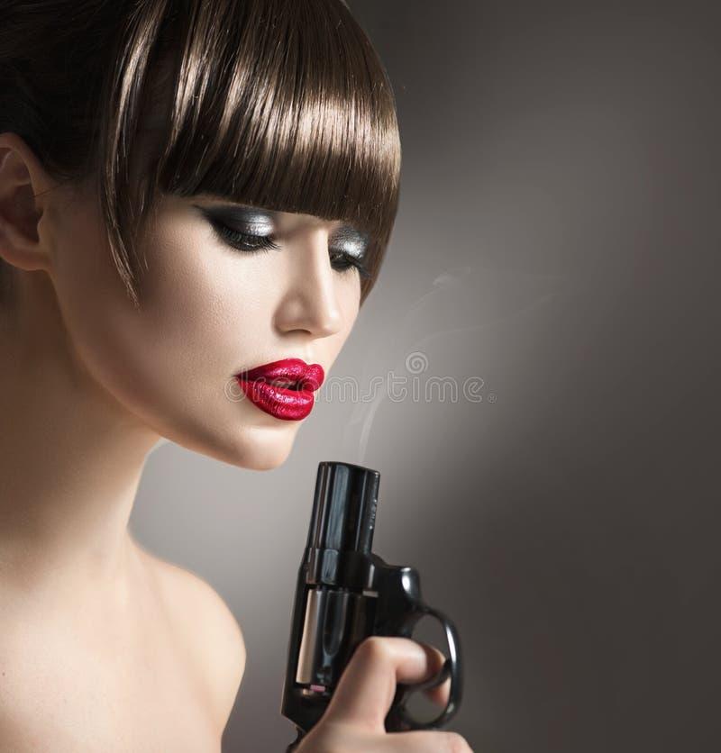 Προκλητική πρότυπη γυναίκα με ένα πυροβόλο όπλο στοκ φωτογραφία
