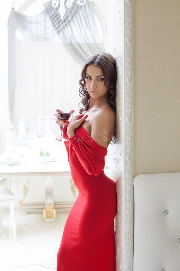 Προκλητική τοποθέτηση κοριτσιών στο κόκκινο φόρεμα με το ποτήρι του κρασιού στοκ εικόνα