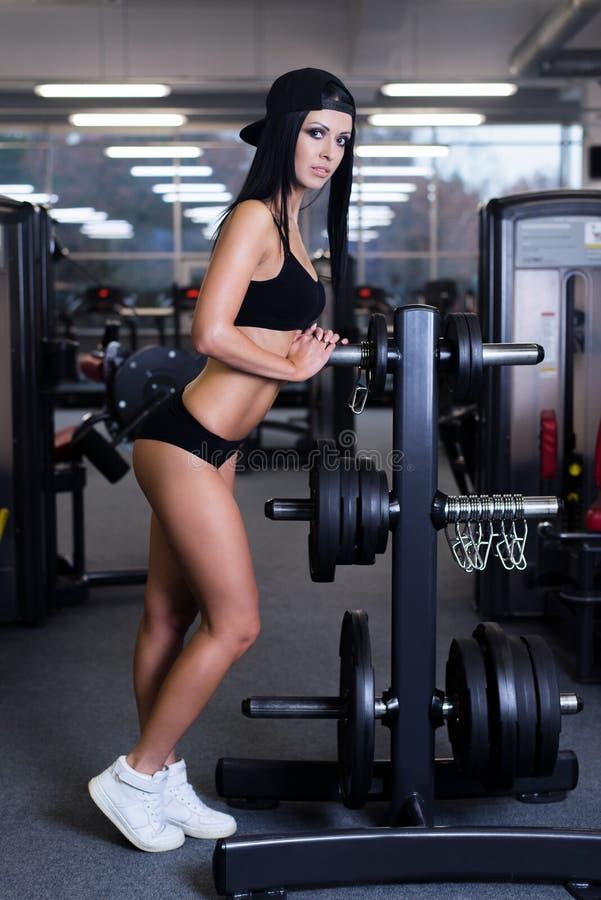 Προκλητική φίλαθλη γυναίκα που κάνει την άσκηση ικανότητας δύναμης στην αθλητική γυμναστική Όμορφο κορίτσι που επιλύει στη γυμνασ στοκ εικόνες