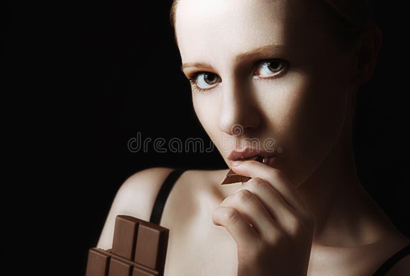 Προκλητική όμορφη νέα γυναίκα που τρώει τη σοκολάτα σε ένα σκοτάδι στοκ φωτογραφία