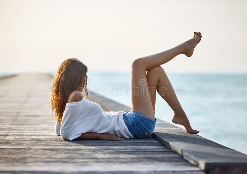 Προκλητική όμορφη χαλάρωση γυναικών στην αποβάθρα με την άποψη θάλασσας στοκ εικόνα με δικαίωμα ελεύθερης χρήσης