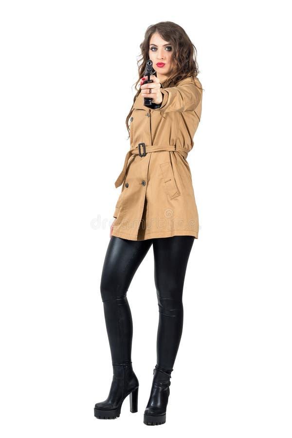 Προκλητικός επικίνδυνος κυματιστός κατάσκοπος τρίχας που φορά το παλτό που στοχεύει το όπλο στη κάμερα στοκ εικόνα