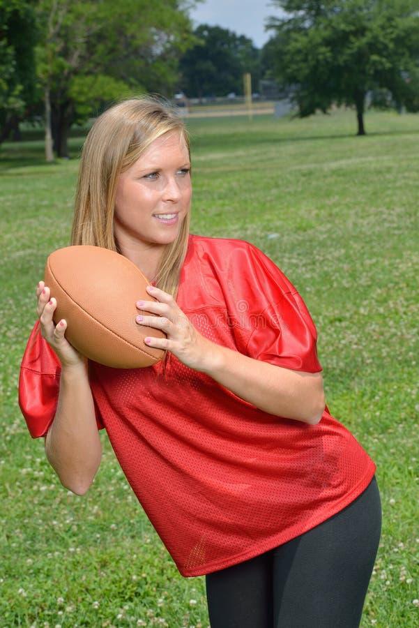 Προκλητικός ξανθός φορέας αμερικανικού ποδοσφαίρου γυναικών στοκ εικόνες