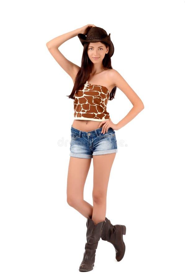 Προκλητικό αμερικανικό cowgirl με τα σορτς και τις μπότες και ένα καπέλο κάουμποϋ. στοκ φωτογραφίες