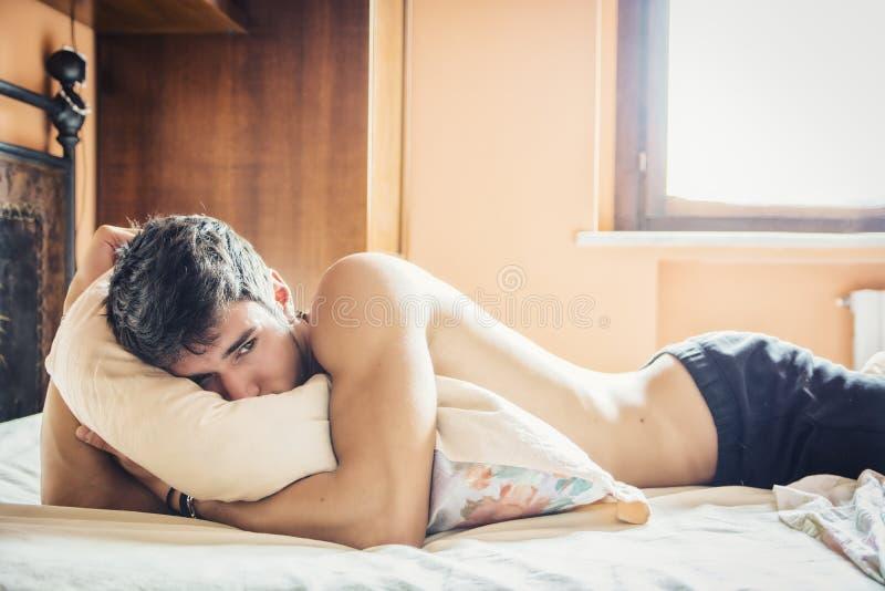 Προκλητικό αρσενικό πρότυπο γυμνοστήθων που βρίσκεται μόνο στο κρεβάτι του στοκ φωτογραφία