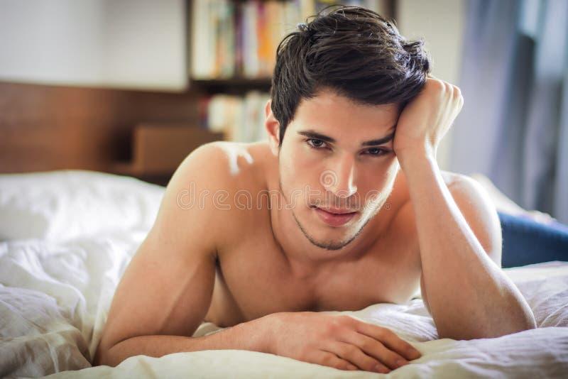 Προκλητικό αρσενικό πρότυπο γυμνοστήθων που βρίσκεται μόνο στο κρεβάτι του στοκ φωτογραφία με δικαίωμα ελεύθερης χρήσης