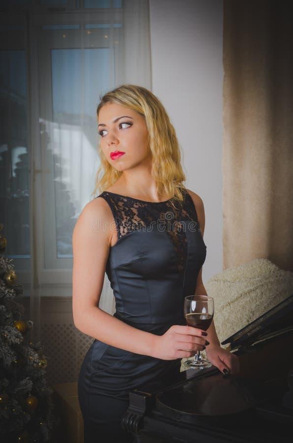 Προκλητικό κορίτσι στο μαύρο φόρεμα το βράδυ, Παραμονή Χριστουγέννων, με ένα ποτήρι του κρασιού στοκ φωτογραφία