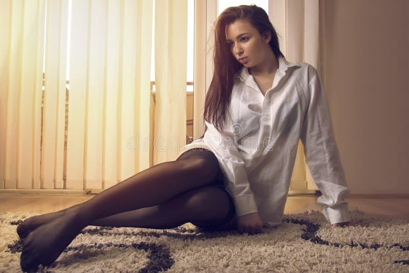 Προκλητικό κορίτσι στο πάτωμα στοκ εικόνες
