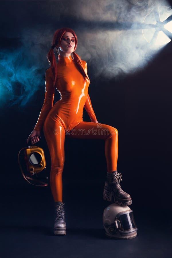 Προκλητικό κορίτσι στο πορτοκαλί λατέξ catsuit με το κράνος, sci στοκ φωτογραφία