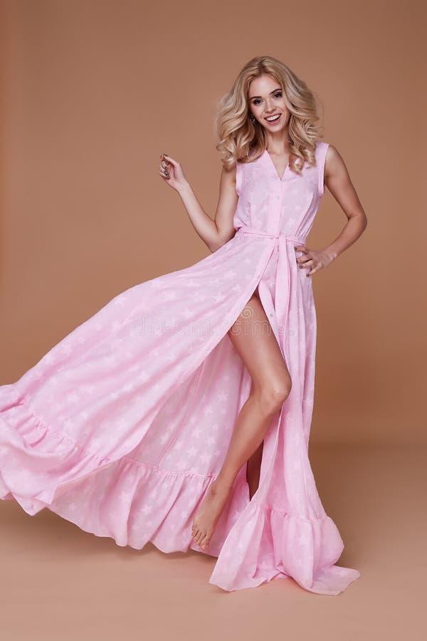 Προκλητικό ομορφιάς γυναικών όμορφο προσώπου μαυρίσματος δερμάτων ένδυσης φόρεμα μεταξιού μωρών ρόδινο στοκ εικόνα
