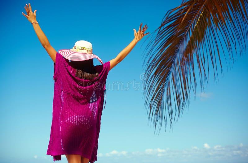 Προκλητικό πρότυπο κορίτσι στο ζωηρόχρωμο ύφασμα και ψαθάκι πίσω από την μπλε παραλία στοκ εικόνες με δικαίωμα ελεύθερης χρήσης