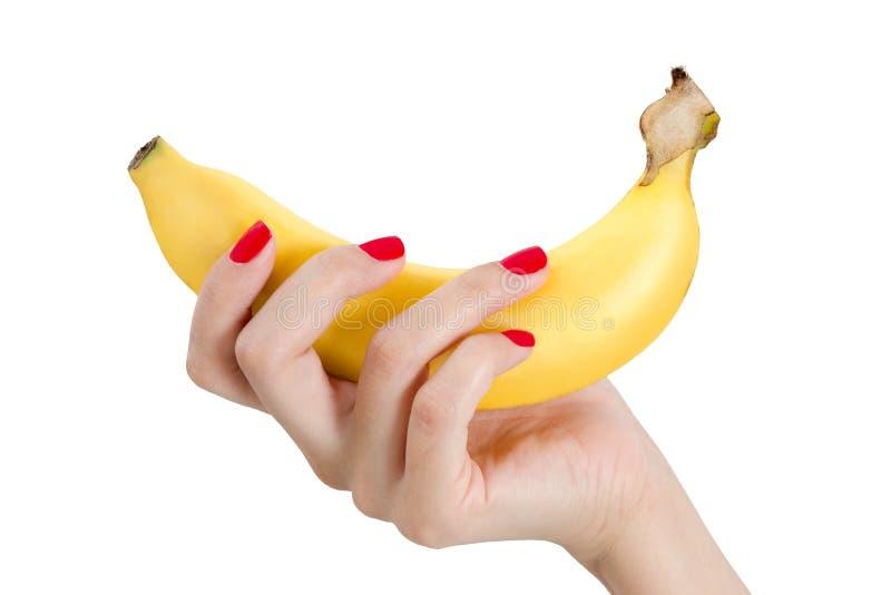 Προκλητικό χέρι γυναικών με τα κόκκινα καρφιά που κρατούν την μπανάνα στοκ εικόνες