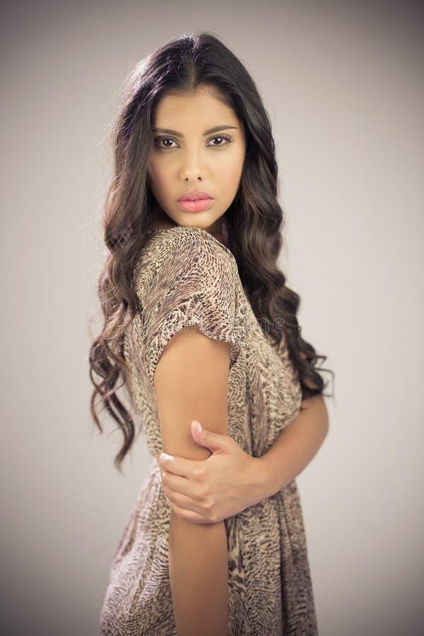 Προκλητικό όμορφο brunette που εξετάζει τη κάμερα σχετικά με το βραχίονα στοκ εικόνες