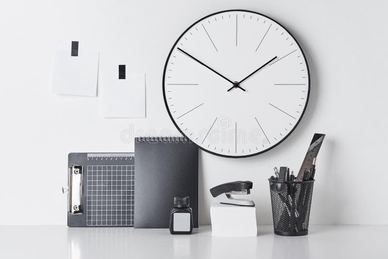 Προμήθειες γραφείων, κολλώδες και στρογγυλό ρολόι στο λευκό στοκ εικόνες με δικαίωμα ελεύθερης χρήσης