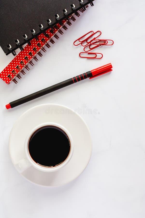 Προμήθειες γραφείων με το σπειροειδή σημειωματάριο, τη μάνδρα, paperclips, και το φλυτζάνι ο στοκ εικόνες με δικαίωμα ελεύθερης χρήσης