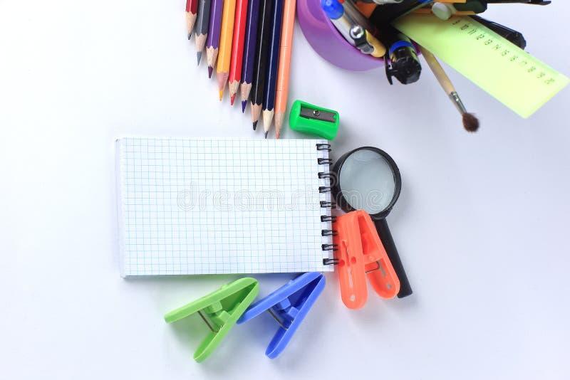 Προμήθειες σημειωματάριων και γραφείων Στην άσπρη ανασκόπηση στοκ εικόνες