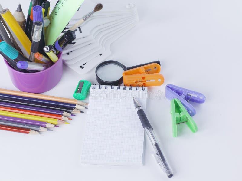 Προμήθειες σημειωματάριων και γραφείων Στην άσπρη ανασκόπηση στοκ εικόνες με δικαίωμα ελεύθερης χρήσης