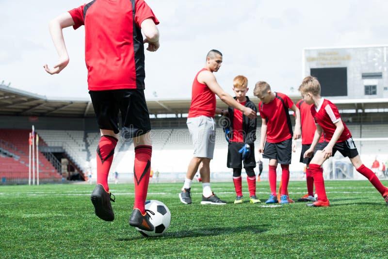 Προπονητής ποδοσφαίρου που συνεργάζεται με τα παιδιά στοκ φωτογραφίες