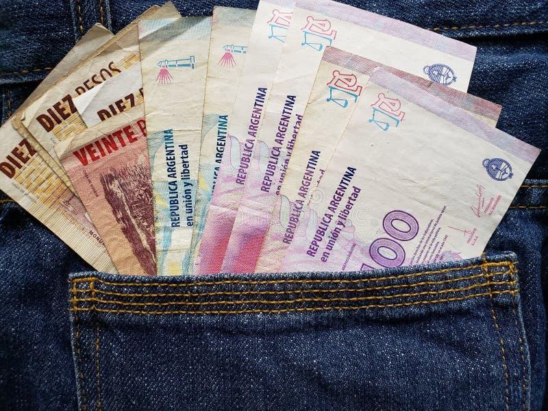 προσέγγιση στην μπροστινή τσέπη των τζιν στο μπλε με τα αργεντινά τραπεζογραμμάτια στοκ εικόνες