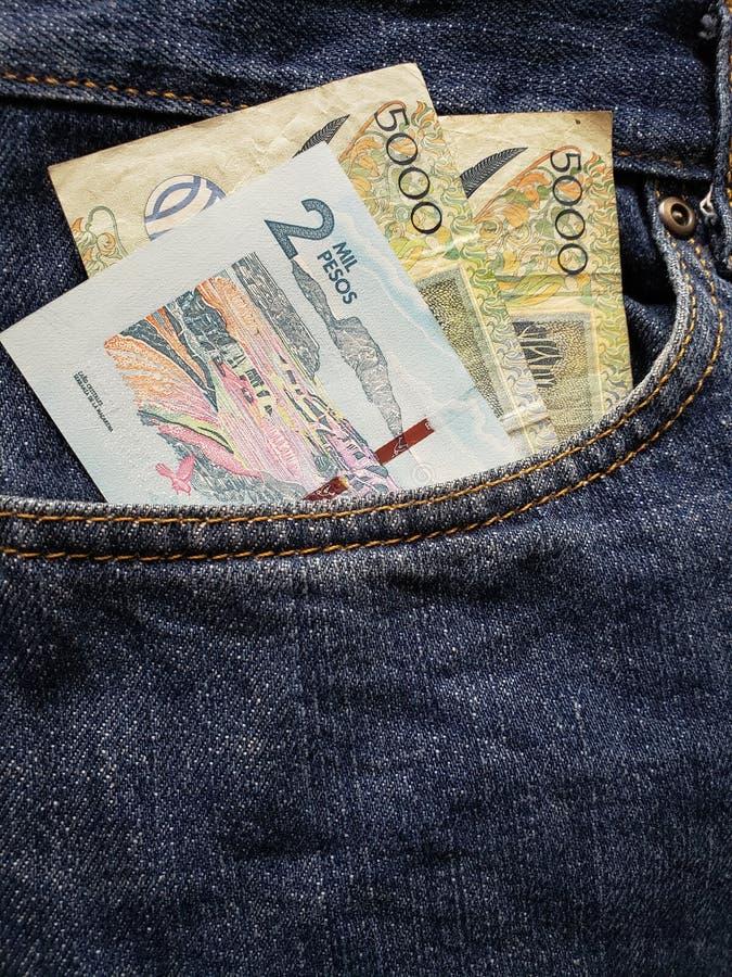 προσέγγιση στην μπροστινή τσέπη των τζιν στο μπλε με τα κολομβιανά τραπεζογραμμάτια στοκ φωτογραφία