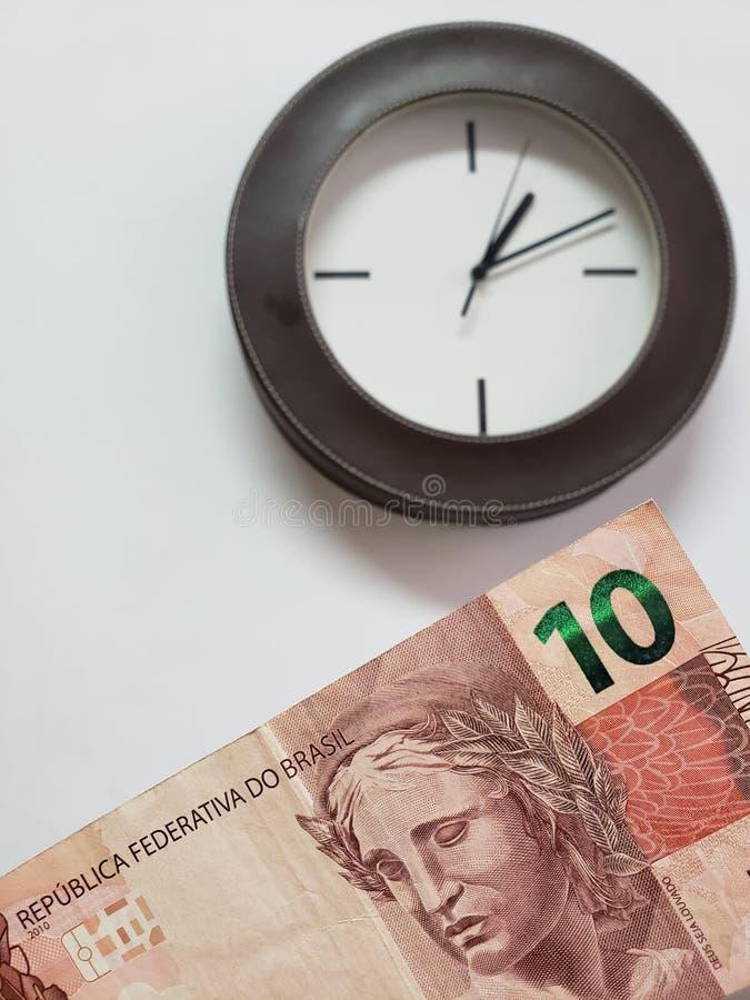 προσέγγιση στο βραζιλιάνο τραπεζογραμμάτιο δέκα reais και υποβάθρου με ένα κυκλικό ρολόι τοίχων στοκ εικόνα με δικαίωμα ελεύθερης χρήσης