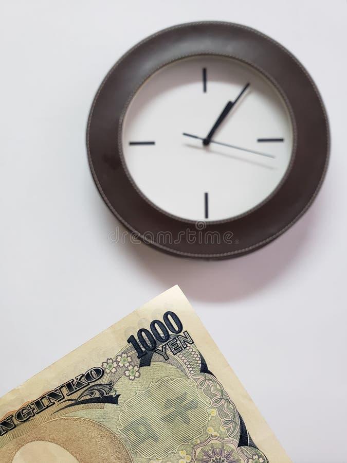 προσέγγιση στο ιαπωνικό τραπεζογραμμάτιο 1000 γεν και του υποβάθρου με ένα κυκλικό ρολόι τοίχων στοκ εικόνα με δικαίωμα ελεύθερης χρήσης
