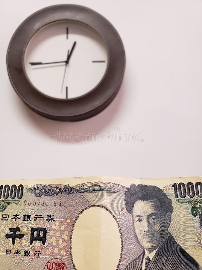 προσέγγιση στο ιαπωνικό τραπεζογραμμάτιο 1000 γεν και του υποβάθρου με ένα κυκλικό ρολόι τοίχων στοκ εικόνες