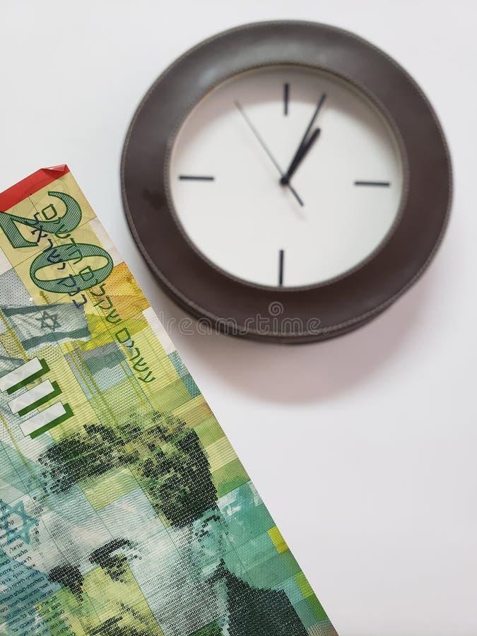 προσέγγιση στο ισραηλινό τραπεζογραμμάτιο είκοσι Shekel και υποβάθρου με ένα κυκλικό ρολόι τοίχων στοκ εικόνες με δικαίωμα ελεύθερης χρήσης