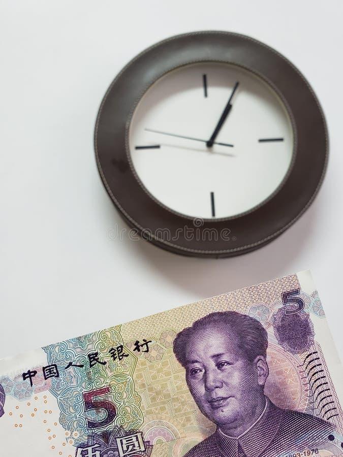 προσέγγιση στο κινεζικό τραπεζογραμμάτιο πέντε yuan και του υποβάθρου με ένα κυκλικό ρολόι τοίχων στοκ φωτογραφία με δικαίωμα ελεύθερης χρήσης